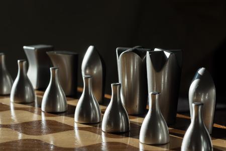 tablero de ajedrez: Madera y brillante de metal gris tablero de ajedrez con piezas iluminada desde el exterior. El juego de ajedrez requiere paciencia y habilidad en el movimiento de las piezas. Usted tiene que ser estratega y planificar los movimientos de antelación