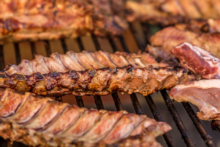 Pork meat grilled on a giant outdoor barbecue on a food market. Grilled meat is more healthy and more tasty than cook meat. Stock Photo
