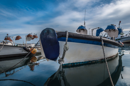 Reflections of fishing boat and a dramatic cloudy blue sky over water in the port of El Serrallo, Tarragona. spain