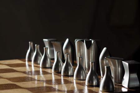 tablero de ajedrez: piezas de madera tablero de ajedrez con metal gris iluminado desde el exterior. El juego de ajedrez requiere paciencia y habilidad en el movimiento de las piezas. Usted tiene que ser estratega y planificar los movimientos de antelación Foto de archivo