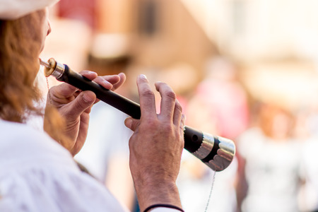 Flautist playing in medieval traditional music group  during medieval market in the town of Montblanc, Tarragona. Spain. Thanks to his music one can feel the atmosphere of a typical medieval market and travel in time, because the flaute was tipically asoc Stock Photo