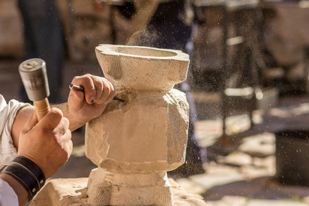 enterprising: Marble master molding a piece of marble at a medieval fair in Tarragona, Spain. The pieces of marble are somewhat difficult to sell Given Their weight but there are lovers of art esta looking for works of marble Especially for decoration