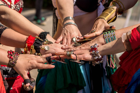 Many dancer?,s hands together showing unity before going dancing. Public outdoor ethnic dancing show on a sunny day