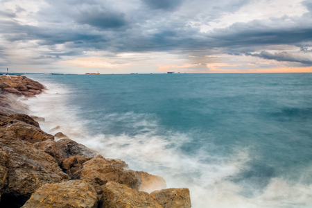 Solitary coastline on a dramatic cloudy day. This breakwater is next to a calm and larg beach, a scene remove common in some parts of the Spanish coastline. This particular breakwater is located near La Pineda, Catalunya. Spain Stock Photo