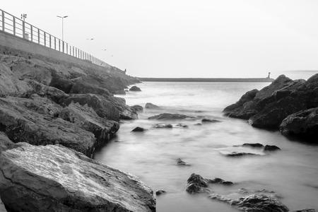 Solitaire golfbreker op een dramatische bewolkte dag. Deze golfbreker ligt naast een kalm en groot strand, een scène die veel voorkomt in sommige delen van de Spaanse kustlijn. Deze specifieke golfbreker bevindt zich in de buurt van Cambrils, Catalunya. Spanje Stockfoto