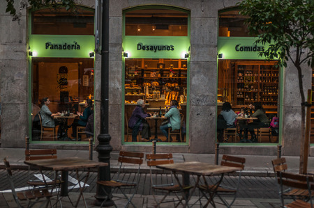 Coffee shop window with its tables full of people.  Madrid, Spain. Europe. December, 14. 2017.