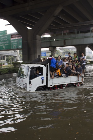 BANGKOK-NOV 5: Unidentified people sit and stand in big truck to escape rising flood waters at Vipavadeerangsit Road, in Bangkok, Thailand on November 5, 2011 Stock Photo - 11108954