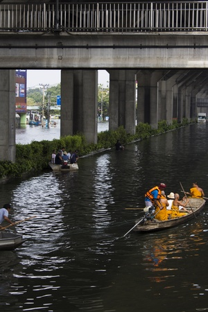 tollway: BANGKOK-NOV 5:Flood hits Bangkok areas around Tollway, Buddhist monks take the boat to travel affected by flood on November 5, 2011 on vibhavadee Rd,Thailand (Donmuang Area)