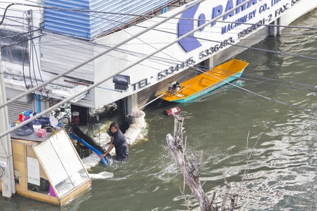 tollway: BANGKOK-NOV 5:Flood hits Bangkok areas around Tollway, Victims are pumping water out of the building on November 5, 2011 on vibhavadee Rd,Thailand (Donmuang Area)