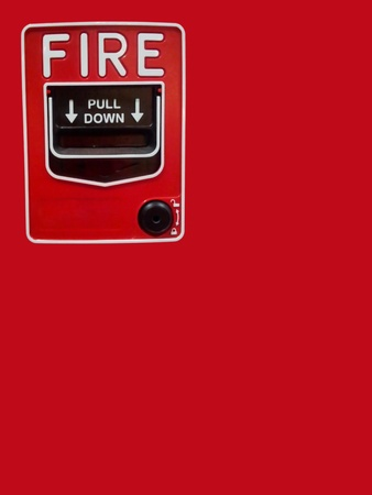 Fire alarm with handle isolated over a red background photo