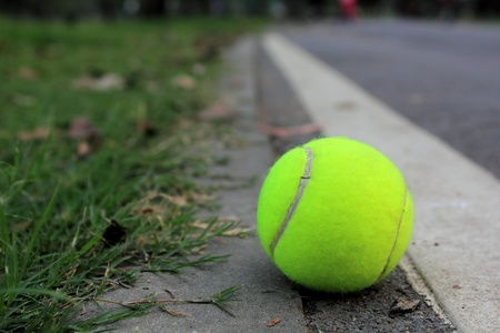 Tennis ball on in the street near a lawn in park