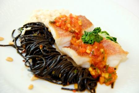 calamar: Espagueti con tinta de calamar y salsa de tomate salmón Foto de archivo