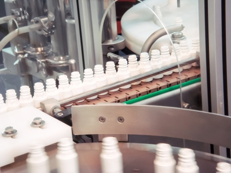 processing speed: Plastic bottle on the conveyor in the production line Stock Photo
