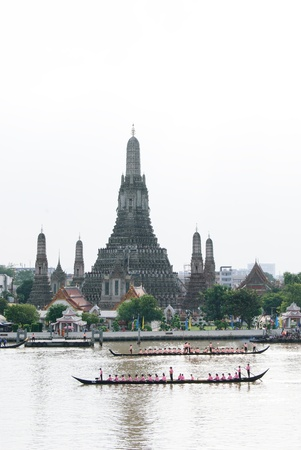 CHAO PHRAYA RIVER, BANGKOK, THAILAND – OCTOBER 19: The 6th Practice of Thai Royal Barge procession cruises down the Chao Phraya river with Wat Arun in the background to celebrate 85th King of Thailand on the throne (December 5, 2012) in Bangkok, Thailan