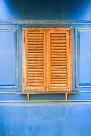 Wooden window with blue wall background photo