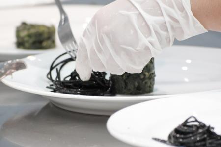 Nahaufnahme von Koch Dekoration Schwarze Spaghetti auf dem Teller