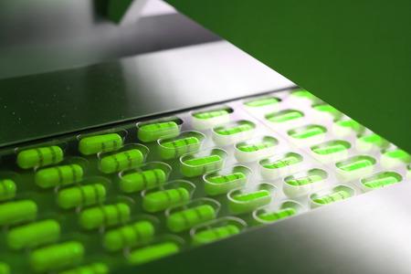 Cápsulas verdes envasadas en forma de tableta máquina de embalaje Foto de archivo