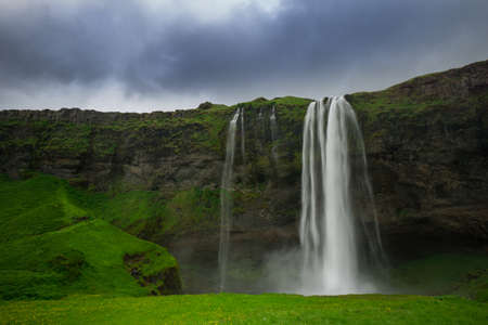Iceland - Waterfall of Seljalandsfoss with green meadow