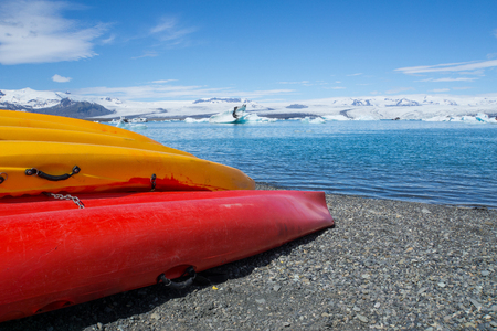 Iceland - Canoes at beach of glacial lake with blue sky