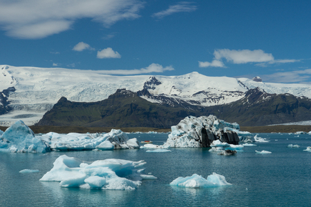 Iceland - Giant ice floes with boat and glacier mountains in background