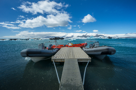 Iceland - Landing stage with three rubber boats in turquoise clear water