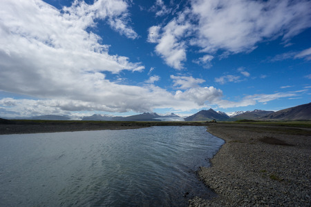 Iceland - Two glaciers behind river in mountainous volcanic landscape