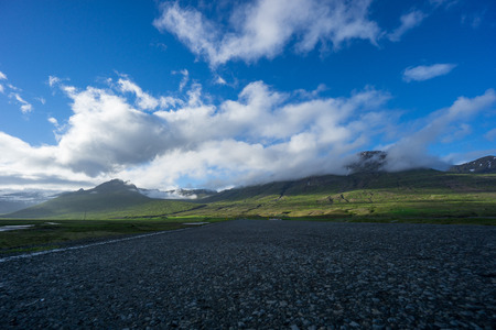 Iceland - Empty endless highway route 1 at shining green mountains Stock Photo