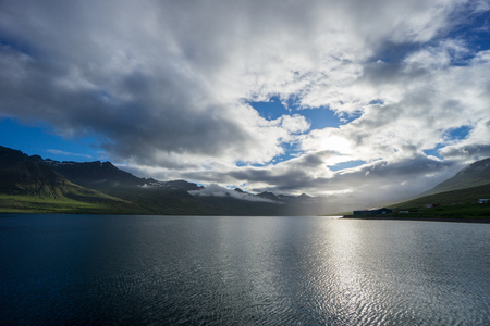 Iceland - Magical dawning light over fjord between green mountains