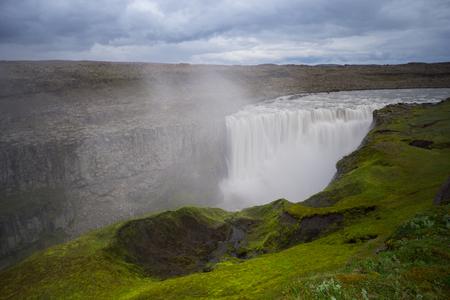 アイスランド - 緑の苔の覆われている領域の背後に途方もない detifoss 滝の上
