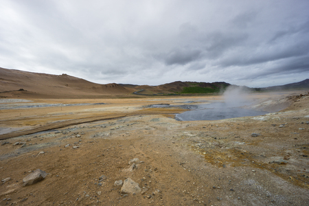 Iceland - Boiling hot mud pot at geothermal area hverir with volcanic colorful mountains