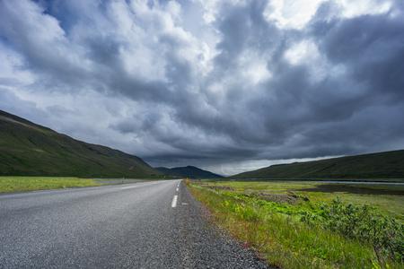 IJsland - Weg door groene vallei en rivier met regen ver weg Stockfoto