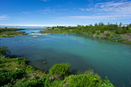 Iceland - Turquoise water of river between green plants flowing into the ocean