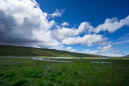 Iceland - Natural stream course through untouched wide green landscape with arriving thunderstorm Stock Photo