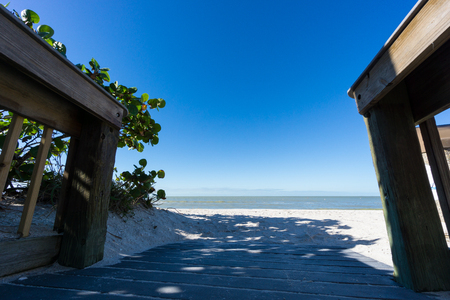 USA, Florida, Perfect white barefoot sand beach with blue sky behind wooden runway