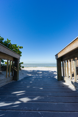 USA, Florida, Wooden runway to perfect white barefoot sand beach with blue sky Banco de Imagens