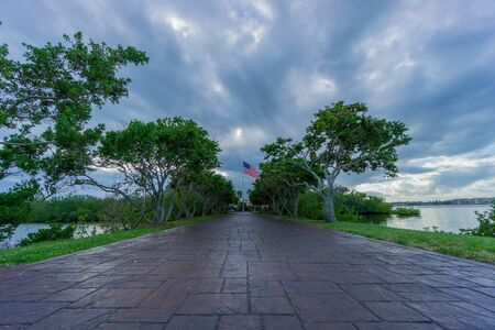 USA, Florida, Path of paver through alley of ancient trees between water with flag of usa behind