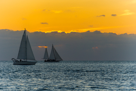 USA, Florida, Orange sunset behind clouds at key west with two sailing boats on the water