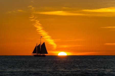 USA, Florida, Ancient sailing boat next to fantastic orange sunset