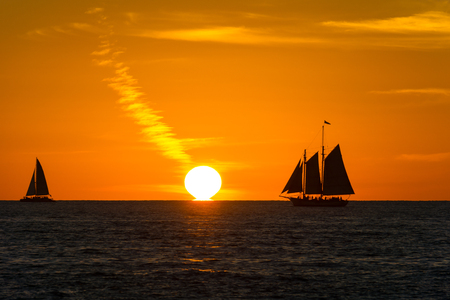 USA, Florida, Two sailboats next to the sun as sunset on ocean
