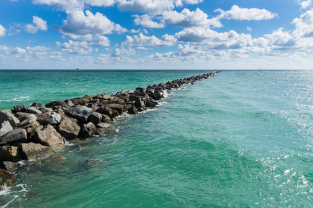 USA, Florida, Miami beach mole of rocks in the turquoise ocean