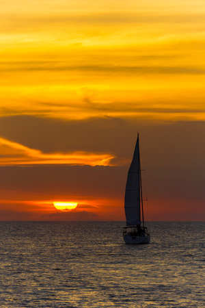 USA, Florida, Amazing orange sunset sky with sailboat on ocean water 写真素材