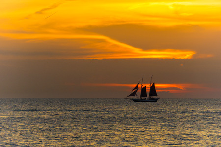 USA, Florida, Red colorful dramatic sunset behind sailing ship