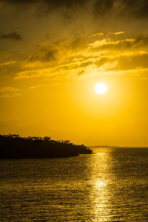 USA, Florida, Intense orange colorful sun reflection on ocean water