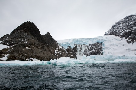 icecaps in the Antarctica with iceberg in the ocean swimming around and melting in the sea Foto de archivo