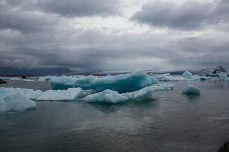 on the sea you can see melting ice bergs floating over the ocean in iceland