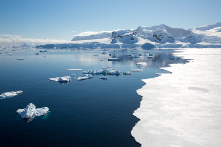 icecaps in the Antarctica with iceberg in the ocean swimming around and melting in the sea Imagens