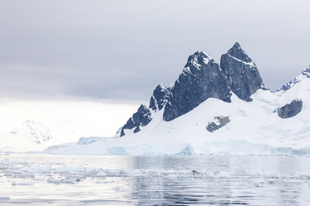 icecaps in the Antarctica with iceberg in the ocean swimming around and melting in the sea Stock fotó
