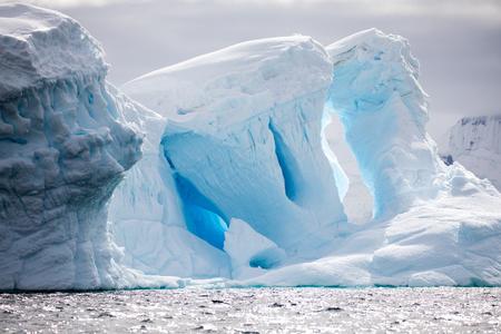Eiskappen in der Antarktis mit Eisberg im Ozean, der herumschwimmt und im Meer schmilzt