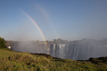 a big river in africa with a waterfall in the mountains makes rainbows