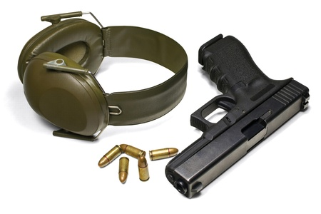 Pistol, ear protection and ammunition isolated on white photo